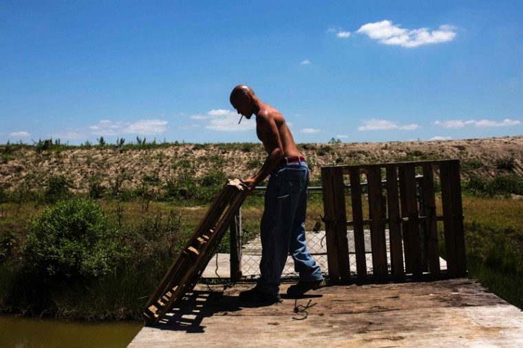 Mel Guidry, born and raised in Pointe aux Chene, opens the gate that leads to the levee near his property on Pointe aux Chene on May 7 ,2017. Mel says things don't look the same as they did when he was a kid. He says he used to play behind the house, an area now covered by water. (AMIR LEVY/AFP/Getty Images)