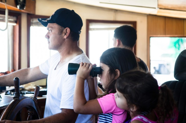 Brent Verdin sails his boat in Pointe Aux Chene bayous while his granddaughter, Brooklyn looks through the binoculars on May 7, 2017, near Isle de Jean Charles. (AMIR LEVY/AFP/Getty Images)