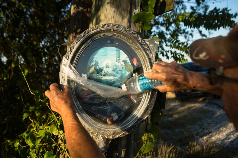 Emray Naquin, 82, shows a clock hanging on a tree in Isle de Jean Charles on May 6, 2017. (Amir LEVYAMIR LEVY/AFP/Getty Images)