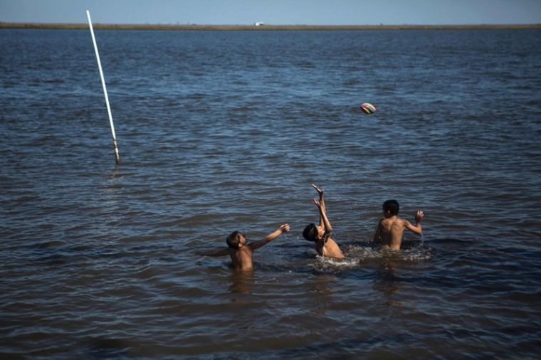 Kids playing ball in a lake in Pointe aux Chenes on May 7, 2017 near Isle de Jean Charles. (AMIR LEVY/AFP/Getty Images)