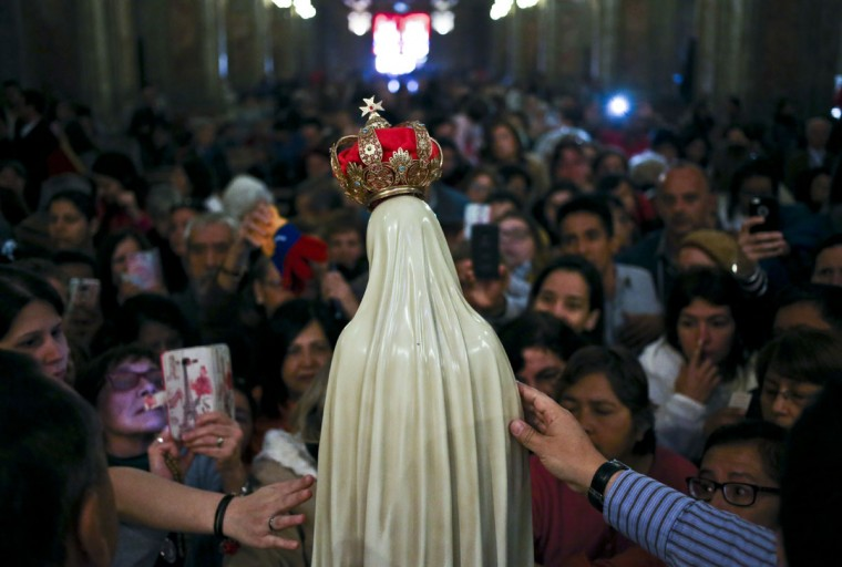 Believers reach out to touch a statue of Our Lady of Fatima after a Mass in her honor at the Metropolitan Cathedral, in Santiago, Chile, Saturday, May 13, 2017. (AP Photo/Esteban Felix)