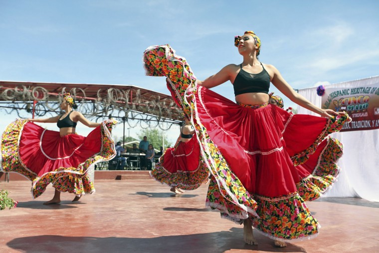FILE - In this May 5, 2016, file photo, Minerva Allende, right, dances with her fellow dancers of Cuerpo Escena Comania de Danza from the Institute of Chihuahua in celebration of Cinco de Mayo at the LULAC/Hispanic Heritage of Odessa's annual Fiesta Lunch at the La Margarita Festival Grounds in Odessa, Texas. Trump's immigration policies and rhetoric are leaving some Mexican Americans and immigrants feeling at odds with a day they already thought was appropriated by beer and liquor companies, event promoters and local bars. (Jacob Ford/Odessa American via AP)