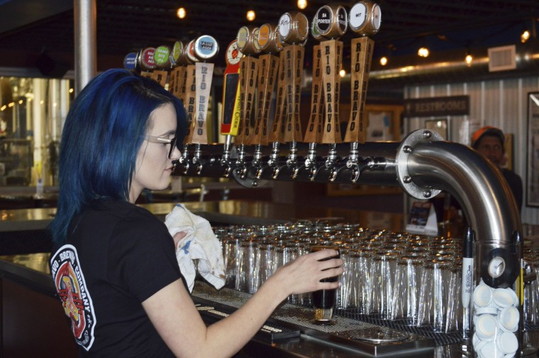 Maya Martinez, a manager at the Rio Bravo Brewing Company in Albuquerque, N.M., pours a craft beer on Wednesday, May 3, 2017, just days before the brewery was set to unveil a new beer on Cinco de Mayo. President Donald Trump's immigration policies and rhetoric are leaving some Mexican Americans and immigrants feeling at odds with a day they already thought was appropriated by beer and liquor companies, event promoters and local bars. (AP Photo/Russell Contreras)