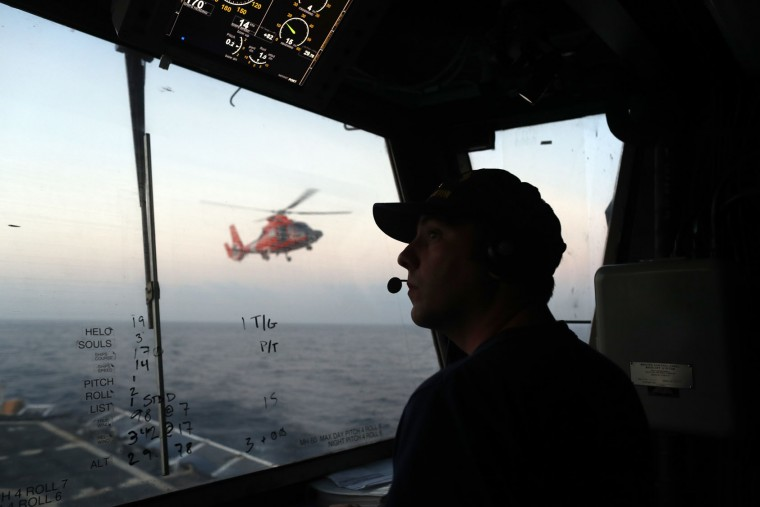 In this March 2, 2017 photo, an unidentified U.S. Coast Guardsman communicates with the pilot of a helicopter during take-off and landing exercises on the U.S. Coast Guard cutter Stratton in the eastern Pacific Ocean. For its drug interdiction operations, the Coast Guard is bringing more intelligence and technology to bear. Deep within the Stratton, specialists crunch data from radar, infrared video,helicopter sorties as well as other available sources. (AP Photo/Dario Lopez-Mills)