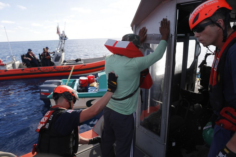 In this Feb. 23, 2017 photo, a U.S. Coast Guard law enforcement team from the USCG cutter Stratton detain four men who were caught on a small fishing boat carrying close to 700 kilos of pure cocaine, in the Pacific Ocean hundreds of miles south of the Guatemala-El Salvador border. Hidden in the bales of cocaine was a GPS tracking device wrapped inside a condom, a sure sign the drug bosses behind the shipment knew right away it didn't reach its destination. (AP Photo/Dario Lopez-Mills)