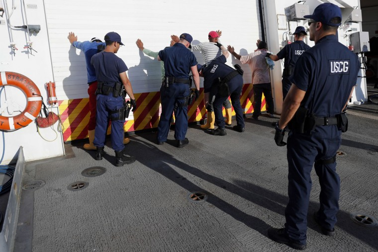 In this Thursday, Feb. 23, 2017 photo, four men who were caught transporting close to 700 kilos of cocaine in a small fishing boat are frisked in the flight deck of the U.S. Coast Guard cutter Stratton after they were detained the in Pacific Ocean, hundreds of miles south of the Guatemala-El Salvador border.(AP Photo/Dario Lopez-Mills)