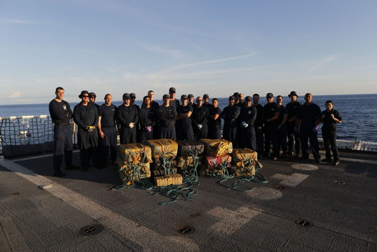 In this Feb. 23, 2017 photo, part of the crew from the U.S. Coast Guard cutter Stratton stand for a photo in front of close to 700 kilograms of pure cocaine that were seized from a small fishing boat in Pacific Ocean, hundreds of miles south of the Guatemala-El Salvador border. Four men, two from Colombia and two from Ecuador were also detained in the operation. (AP Photo/Dario Lopez-Mills)