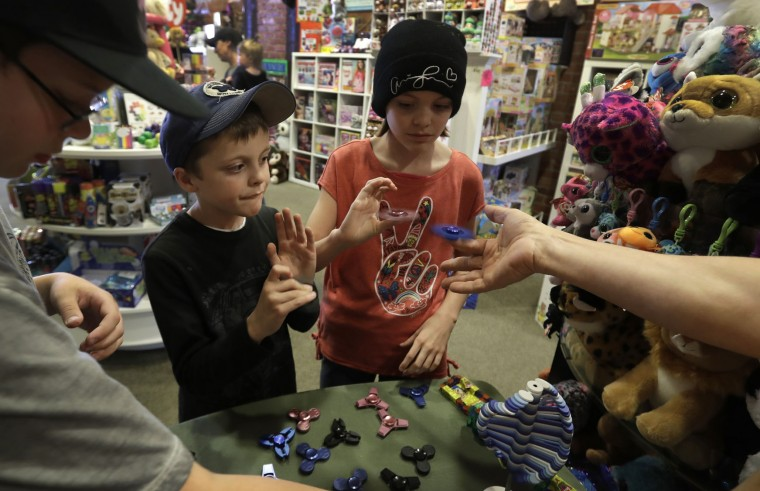 In this Thursday, May 11, 2017, photo, customers look over the selection of fidget spinners at the Funky Monkey Toys store in Oxford, Mich. Stores can't keep them in stock and parents are going crazy trying to find them. (AP Photo/Carlos Osorio)