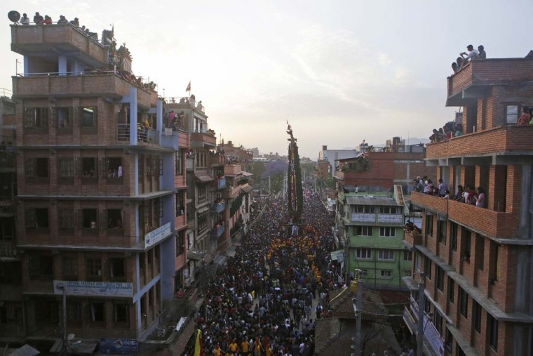 In this April 30, 2017, photo, devotees fill the streets in the Rato Machindranath Chariot festival in Lalitpur, Nepal. Lines of followers pull on two thick ropes to move the massive chariot along the narrow roads of Patan. With no steering or brakes, men throw wooden blocks under the wheels to turn or stop it. The harvest festival, that centers on the chariot in the capital city Kathmandu, preludes the monsoon season in Nepal where majority of the population still depend on farming for livelihood. (AP Photo/Niranjan Shrestha)