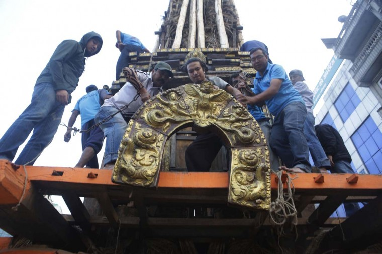 In this April 27, 2017 photo, members of the Barahi community construct the Rato Machindranath Chariot in Lalitpur, Nepal. The wooden chariot is built to appease the gods in hopes of being blessed with a good rainfall followed by a bountiful harvest. The Barahis are responsible for repairing the giant wheels, carving the base and erecting the tower of logs for the chariot. (AP Photo/Niranjan Shrestha)