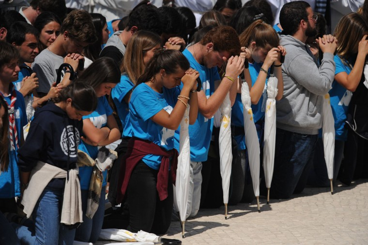 Worshipers kneel in prayer during a Mass at the Sanctuary of Our Lady of Fatima where Pope Francis canonized Jacinta and Francisco Marto in Fatima, Portugal. (AP Photo/Paulo Duarte)