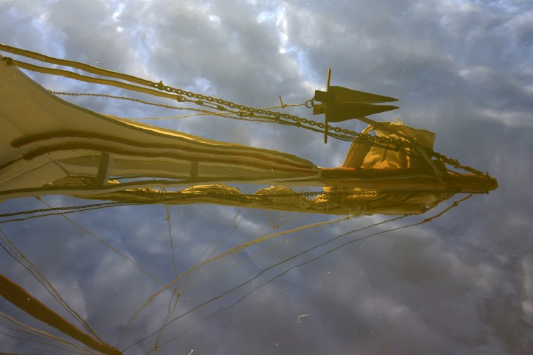 A reflection of the mast of the H.M Krentz, an authentic working skipjack, is seen in the Miles River at Navy Point. (Algerina Perna/Baltimore Sun)