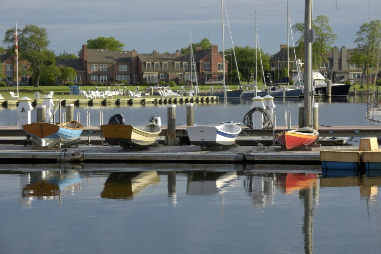 Rowing skiffs sit on a floating dock at Chesapeake Bay Maritime Museum on the Miles River at Navy Point with the Perry Cabin Townhouses in the background.  (Algerina Perna/Baltimore Sun)