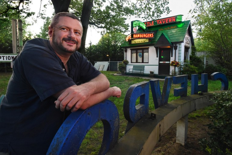 Norman James, 52, leans against the Luby Chevrolet sign, in his private backyard sign garden. He transformed a shed into an accurate replica of a Little Tavern to showcase his restored neon signs from the popular hamburger chain. (Amy Davis / Baltimore Sun)