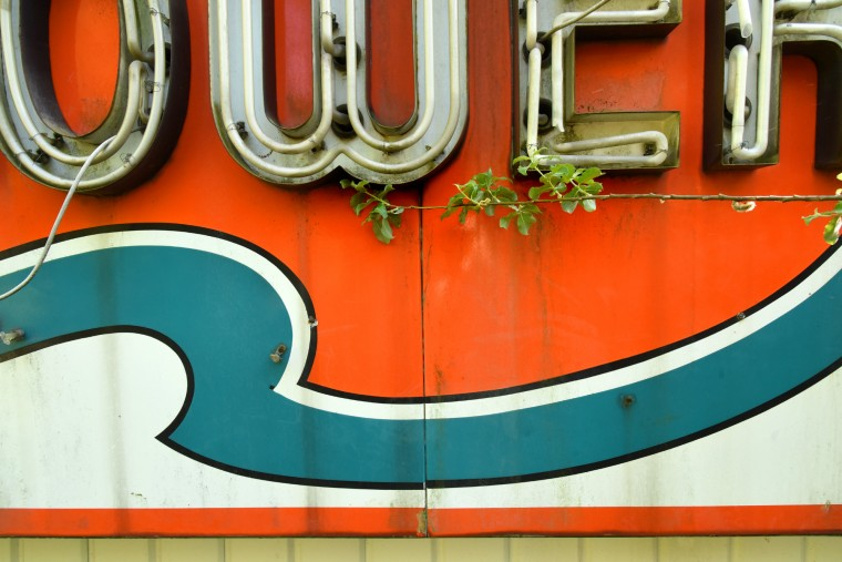 A tree branch encroaches on part of a porcelain enamel sign from a White Tower hamburger chain restaurant at Washington Boulevard and South Monroe Street, near Montgomery Ward. (Amy Davis / Baltimore Sun)