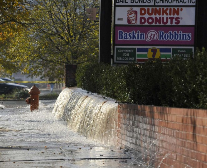 Water rushes over a brick wall at the Mount Vernon Marketplace from a broken water main near the intersection of Madison Street and Guilford Avenue on Nov. 12, 2012. (Robert K. Hamilton/Baltimore Sun)