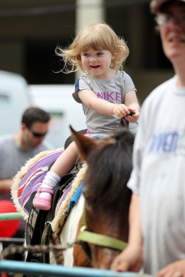 Staff Photo by Jen Rynda Maggie Mininger, 2, of Timonium smiles as she goes for a pony ride during Towsontown Spring Festival in Towson, MD on Saturday, May 5, 2012.