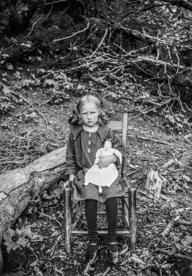 Seated on a chair near fallen trees, a girl posed with her doll. Many of the adults and children in Taylor's undated photographs have not been identifie