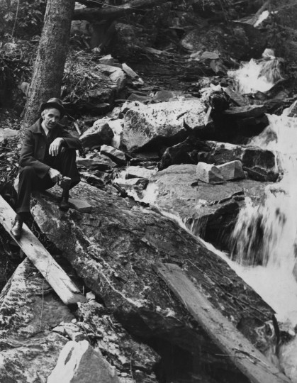 Later in his life, year unknown, Finley Taylor posed for this photograph by a cascading mountain spring. He died in 1976.