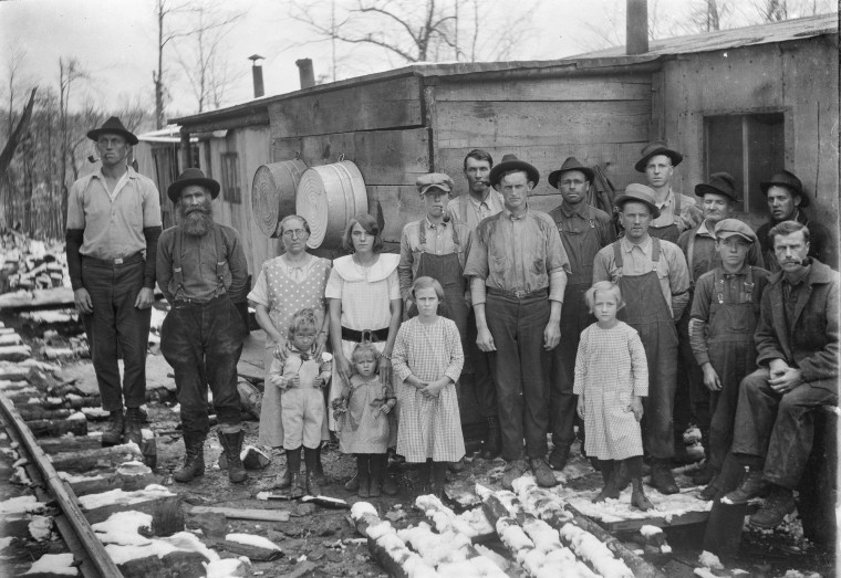 An extended family of loggers posed for Finley Taylor outside their shanty home on a winter's day, year unknown.