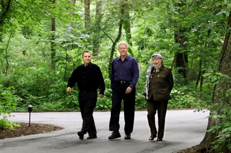 President Clinton, Israeli Prime Minister Ehud Barak, left, and Palestinian leader Yasser Arafat, right, walk on the grounds of Camp David, Md., in this July 11, 2000, file photo at the start of the Mideast summit. Named Shangri-La by President Franklin Roosevelt in 1942, the secluded mountain sanctuary 60 miles north of Washington has been far more than just a presidential retreat. (AP Photo/Ron Edmonds/File)