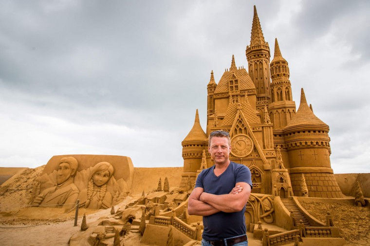 Alexander Deman, the organiser of Disney Sand Magic, poses in front of sand sculptures representing characters and scenes of Disney movies during an exhibition Disney Sand Magic in Ostende, on June 29, 2017. (AFP Photo/ Aurore Belot)