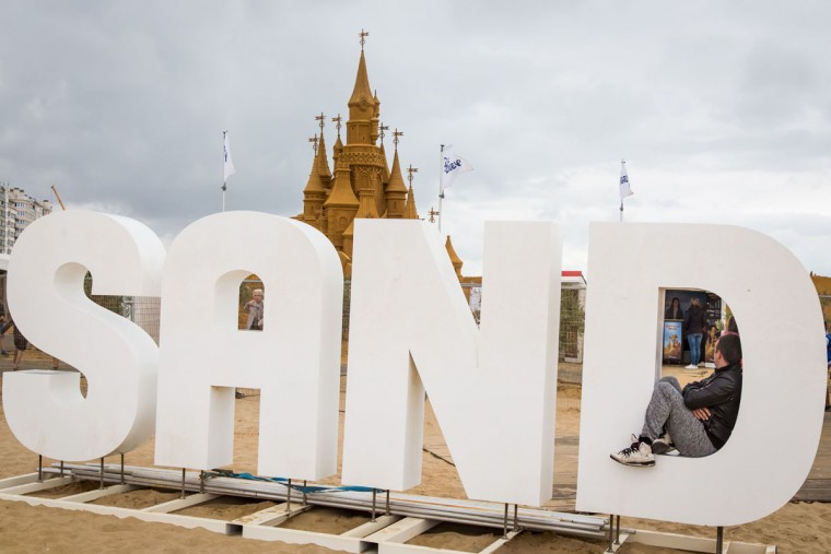 A man sits in a giant letter in front of sand sculptures representing characters and scenes of Disney movies during an exhibition Disney Sand Magic in Ostend on June 29, 2017. (AFP Photo/ Aurore Belot)
