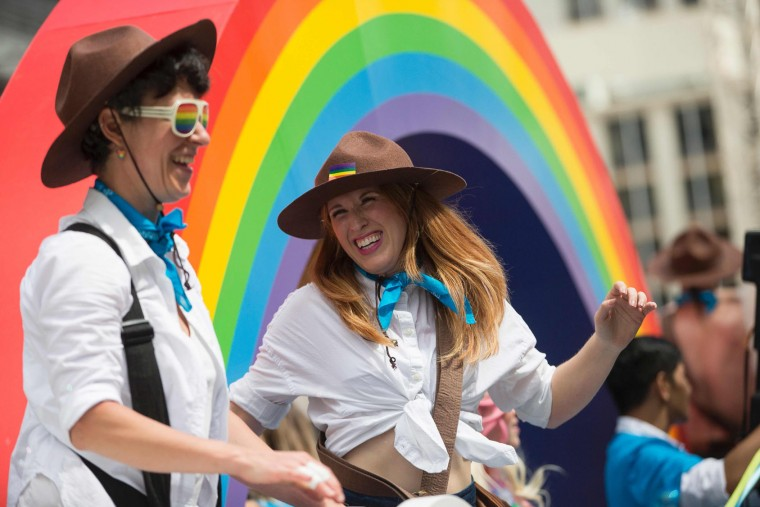 "Women with ""Mountie"" hats dance on a float during the Pride Parade in Toronto, Ontario, June 25, 2017. The event draws hundreds of thousands of spectators every year. (Geoff Robins/AFP/Getty Images)"