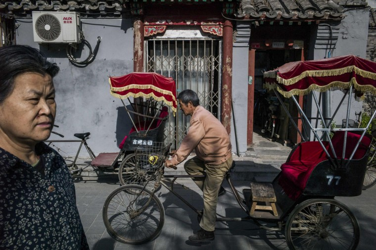 This photo taken on April 23, 2017 shows a rickshaw driver riding in a touristic area in Beijing. Appearing in China at the end of the 19th century, rickshaws originally had two wheels and were pulled by their driver on foot, with passengers seated at the back. Today, most of the vehicles are tricycles - some still have pedals and are propelled by physical force, but the majority are equipped with electric or gas engines. (FRED DUFOUR/AFP/Getty Images)