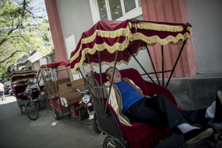 This photo taken on April 23, 2017 shows a rickshaw driver taking a rest in Beijing. Appearing in China at the end of the 19th century, rickshaws originally had two wheels and were pulled by their driver on foot, with passengers seated at the back. Today, most of the vehicles are tricycles - some still have pedals and are propelled by physical force, but the majority are equipped with electric or gas engines. (FRED DUFOUR/AFP/Getty Images)