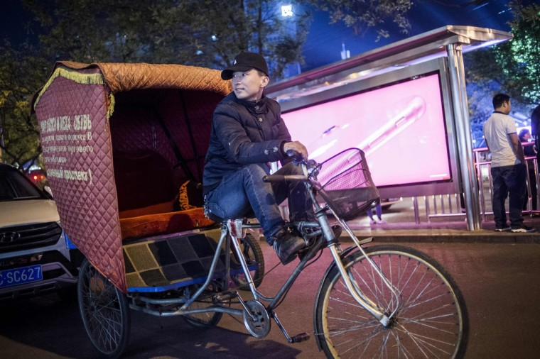 This photo taken on April 24, 2017 shows rickshaw driver Li Wei waiting for clients in the streets of Beijing. Appearing in China at the end of the 19th century, rickshaws originally had two wheels and were pulled by their driver on foot, with passengers seated at the back. Today, most of the vehicles are tricycles - some still have pedals and are propelled by physical force, but the majority are equipped with electric or gas engines. (FRED DUFOUR/AFP/Getty Images)