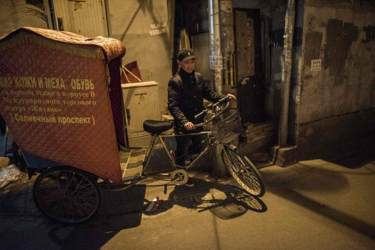 This photo taken on April 24, 2017 shows rickshaw driver Li Wei starting his night shift in the streets of Beijing. Appearing in China at the end of the 19th century, rickshaws originally had two wheels and were pulled by their driver on foot, with passengers seated at the back. Today, most of the vehicles are tricycles - some still have pedals and are propelled by physical force, but the majority are equipped with electric or gas engines. (FRED DUFOUR/AFP/Getty Images)