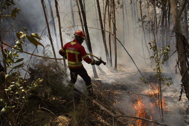 A firefighter battles a fire after a wildfire took dozens of lives on June 20, 2017 near Picha, in Leiria district, Portugal. On Saturday night, a forest fire became uncontrollable in the Leiria district, killing at least 62 people and leaving many injured. Some of the victims died inside their cars as they tried to flee the area. (Photo by Pablo Blazquez Dominguez/Getty Images)