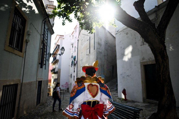 A girl dressed up in tradidional costume walks a street of the typical Lisbon neighborhood of Alfama, prior to attending the Santo Antonio de Lisboa's Parade on Avenida da Liberdade, in Lisbon on June 12, 2017. Lisbon celebrates Saint Anthony's day, the city's protector saint, with a parade that gathers participants from several typical neighborhoods of the city. (Patricia de Melo Moreira/AFP/Getty Images)