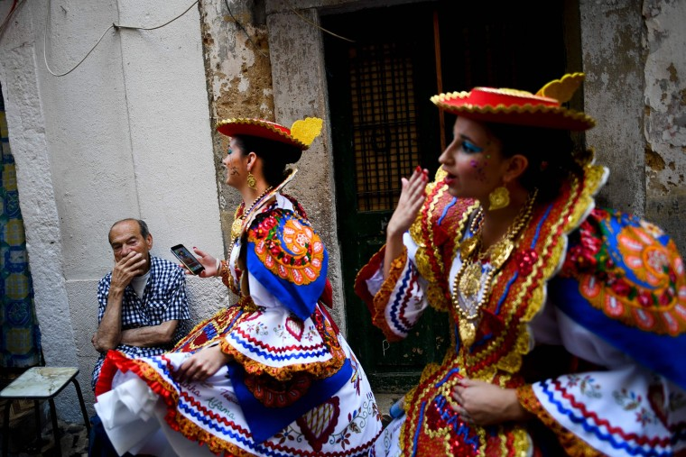 A neighbour of the typical Lisbon neighborhood of Alfama look at two girls dressed up in traditional costumes before atending the Santo Antonio de Lisboa's Parade on Avenida da Liberdade, in Lisbon on June 12, 2017. Lisbon celebrates Saint Anthony's day, the city's protector saint, with a parade that gathers participants from several typical neighborhoods of the city. (Patricia de Melo Moreira/AFP/Getty Images)