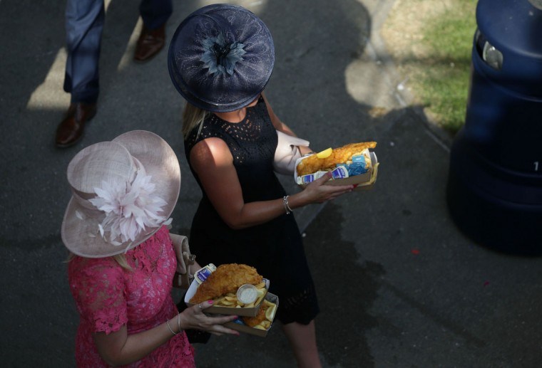Racegoers carry portions of fish and chips on day one of the Royal Ascot horse racing meet, in Ascot, west of London, on June 20, 2017.The five-day meeting is one of the highlights of the horse racing calendar. Horse racing has been held at the famous Berkshire course since 1711 and tradition is a hallmark of the meeting. Top hats and tails remain compulsory in parts of the course while a daily procession of horse-drawn carriages brings the Queen to the course. / (AFP Photo/Daniel Leal-olivas)