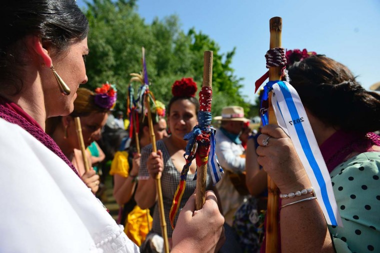 Pilgrims in traditional Rocio costume with a stick with the colors of their brotherhood and a flower in their hair gather near the Quema river during the annual El Rocio pilgrimage in Villamanrique, near Sevilla on June 1, 2017. (CRISTINA QUICLER/AFP/Getty Images)