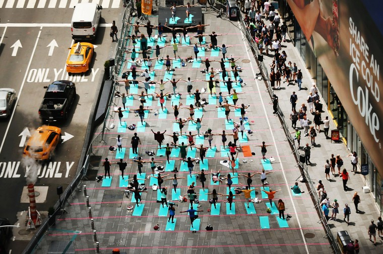Hundreds of yoga enthusiasts participate in a mass yoga class in New York's Times Square to celebrate the summer solstice on June 21, 2017 in New York City. Throughout the day thousands attended the free yoga classes in the heart of Manhattan. Around the world people are celebrating the summer and winter solstices which mark the longest and shortest days of the year. (Photo by Spencer Platt/Getty Images)
