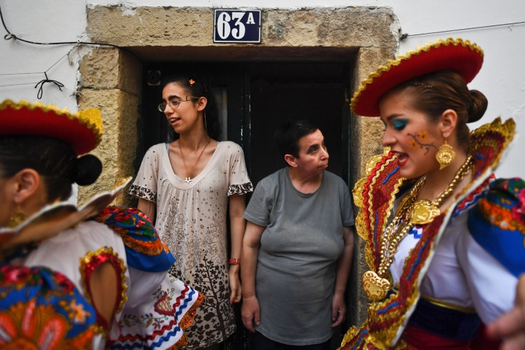 Two neighbours of the typical Lisbon neighborhood of Alfama look at two girls dressed up in traditional costumes before attending the Santo Antonio de Lisboa's Parade on Avenida da Liberdade, in Lisbon on June 12, 2017. Lisbon celebrates Saint Anthony's day, the city's protector saint, with a parade that gathers participants from several typical neighborhoods of the city. (Patricia de Melo Moreira/AFP/Getty Images)