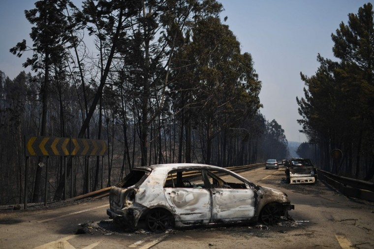 A picture taken on June 18, 2017 shows burnt cars on a road after a wildfire in Figueiro dos Vinhos.A wildfire in central Portugal killed at least 57 people and injured 59 others, most of them burning to death in their cars, the government said on June 18, 2017. Several hundred firefighters and 160 vehicles were dispatched late on June 17 to tackle the blaze, which broke out in the afternoon in the municipality of Pedrogao Grande before spreading fast across several fronts. / (AFP Photo/Patricia Melo moreirapatricia de melo moreira)