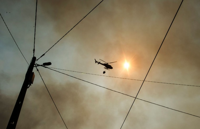 A firefighter helicopter overflies a wildfire in Carvalho, next to Pampilhosa da Serra, on June 19, 2017.More than 1,000 firefighters are still trying to control the huge forest fire that erupted on June 17, 2017 in central Portugal killing at least 62 people and injuring 62 more, many trapped in their cars by the flames, causing a great deal of emotion in the country. / (AFP Photo/Miguel Riopa)