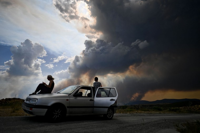 Some people watch the columns of smoke rising from a wildfire in Gois, Coimbra district, on June 20, 2017.The huge forest fire that erupted on June 17, 2017 in central Portugal killed at least 64 people and injured 135 more, with many trapped in their cars by the flames. / (AFP Photo/Patricia Melo moreirapatricia de melo moreira)