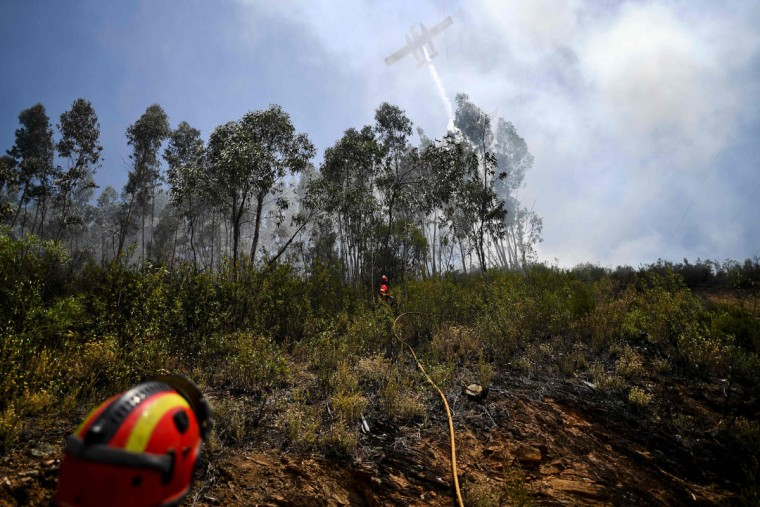 A firefighter plane drops water as Spanish military firefighters from the Emergency Military Unit (UME) work on the ground in Cernache de Bomjardim in Serta on June 20, 2017.The huge forest fire that erupted on June 17, 2017 in central Portugal killed at least 64 people and injured 135 more, with many trapped in their cars by the flames. / (AFP Photo/Patricia Melo moreirapatricia de melo moreira)