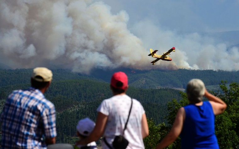 Some locals watch a Canadair plane overflying smoke columns taht raise as wildfires burn close to Pedrogao Pequeno, on June 20, 2017. The huge forest fire that erupted on June 17, 2017 in central Portugal killed at least 64 people and injured 135 more, with many trapped in their cars by the flames. / (AFP Photo/Miguel Riopa)