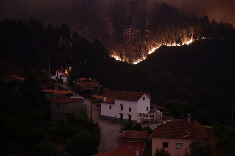 A picture taken on June 18, 2017 shows flames and smoke during a wildfire near the village of Mega Fundeira. Portugal declared three days of national mourning from June 18, 2017 after the most deadly forest fire in its recent history, raging through the centre of the country.The fire, which broke out June 17, 2017 in the Pedrogao Grande district, had killed at least 62 people and injured more than 50, according to the latest official update by Sunday afternoon. / (AFP Photo/Miguel Riopa)