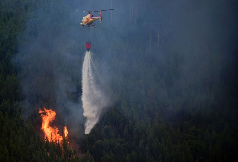 A helicopter drops water over a wildfire in Carvalho, next to Pampilhosa da Serra, on June 19, 2017.More than 1,000 firefighters are still trying to control the huge forest fire that erupted on June 17, 2017 in central Portugal killing at least 62 people and injuring 62 more, many trapped in their cars by the flames, causing a great deal of emotion in the country. / (AFP Photo/Miguel Riopa)