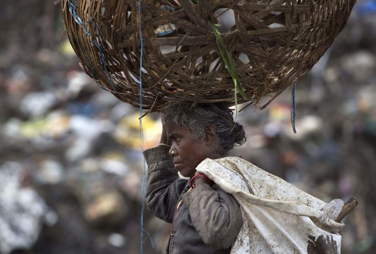 An Indian woman searches for reusable material at a garbage dumping site on World Environment Day in Gauhati, India, Friday, June 5, 2015. The World Environment Day is celebrated on June 5 every year by the United Nations for encouraging worldwide awareness and action for the environment. (AP Photo/Anupam Nath)