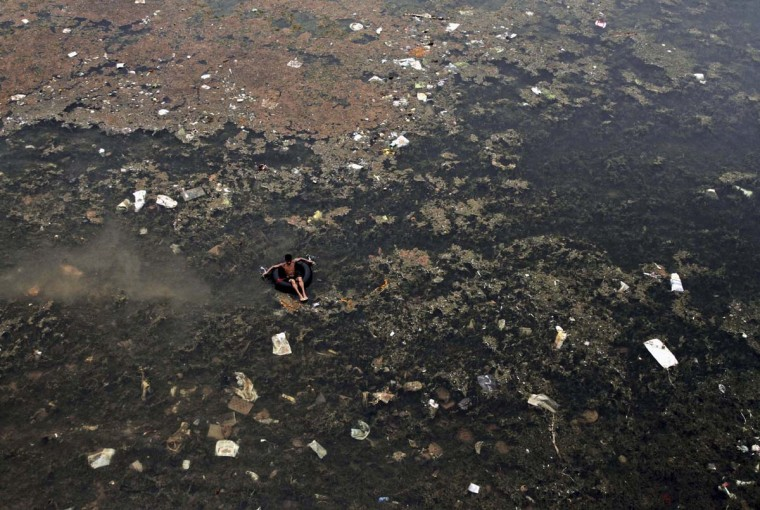A young ragpicker floats on an inflated tube as he searches for recycled materials in the polluted waters of River Kuakhai on World Environment Day on the outskirts of eastern Indian city of Bhubaneswar, India, Friday, June 5, 2015. The World Environment Day is celebrated on June 5 every year by the United Nations for encouraging worldwide awareness and action for the environment. (AP Photo/Biswaranjan Rout)