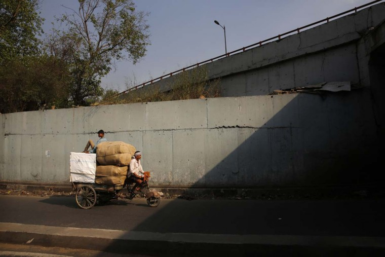 An Indian man carries goods in a home-made modified motorized vehicle in New Delhi, India, Friday, June 5, 2015. The World Environment Day is celebrated on June 5 every year by the United Nations for encouraging worldwide awareness and action for the environment. (AP Photo/Manish Swarup)