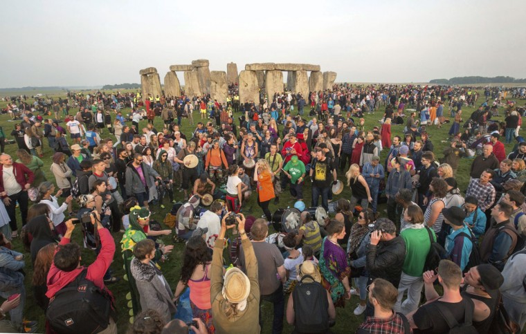 Some thousands of people gather to celebrate the Summer Solstice at Stonehenge in Salisbury, England, at sunrise early Wednesday June 21, 2017. The prehistoric monument, Stonehenge is about 5000-years old and is thought to have been constructed to mark the movement of the sun and other heavenly objects according to Pagan rites. (Steve Parsons/PA via AP)
